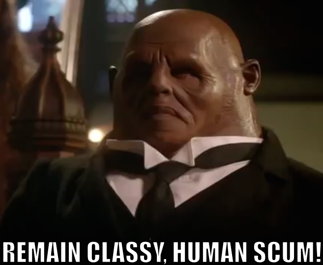 "Strax, wearing a smart suit, says ""REMAIN CLASSY, HUMAN SCUM!"""
